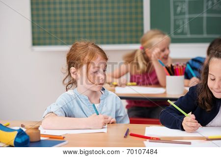 Young Girl On Class Looking At A Classmates Work