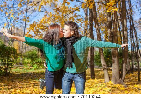 Happy family of two in autumn park on sunny day