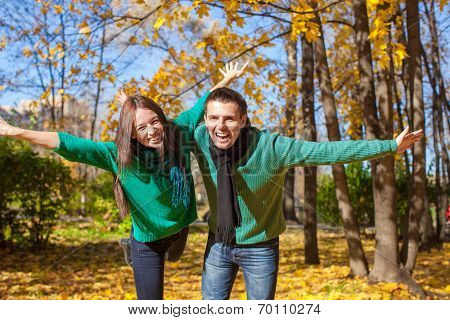 Young couple having fun in autumn park on sunny fall day