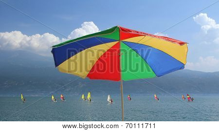 Beach Umbrella In Rainbow Colors And Group Of Windsurfers On Garda Lake