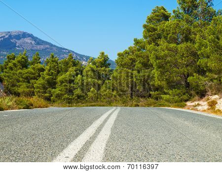 The asphalt road leading through the Rhodes island, Greece.