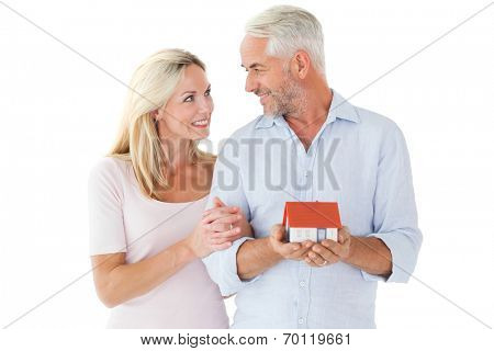 Happy couple holding miniature model house on white background