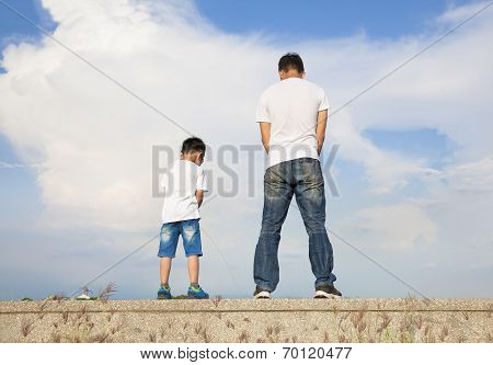 Father And Son Standing On A Stone Platform And Pee Together