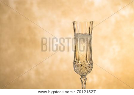 A glass of champagne poised against a gold, mottled background. Room for copy on left side of glass.