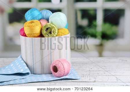 Clews of thread for hook knitting in box on the white table on window background