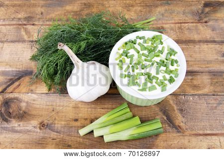 Plastic round bowl of cream with a tuft of dill, onion and garlic near it on wooden background