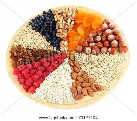 Big round plate with raisins, raspberries, oatmeal, nuts and dried apricots divided on sectors on white background isolated