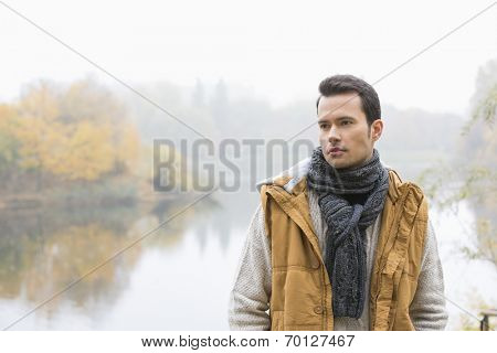 Thoughtful young man in warm clothing standing against lake