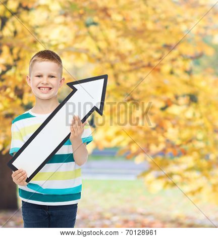 advertising, direction and childhood concept - smiling little boy with white blank arrow pointing up over autumn park background