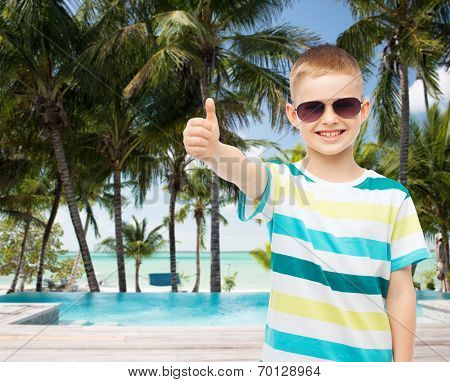 childhood, travel, summer vacation, gesture and people concept - smiling little boy wearing sunglasses over beach background