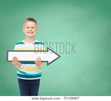 advertising, direction, education and childhood concept - smiling little boy with white blank arrow over green board background