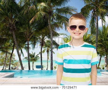 childhood, summer, travel, vacation and people concept - smiling little boy wearing sunglasses over pool and beach background
