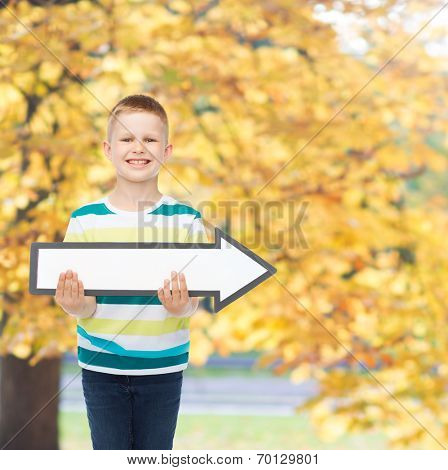 advertising, direction and childhood concept - smiling little boy with white blank arrow pointing right over autumn park background