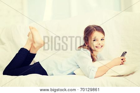 home, leisure, technology and internet concept - little student girl with smartphone at home