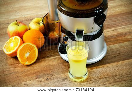 Juicer And Orange Juice On Wooden Background