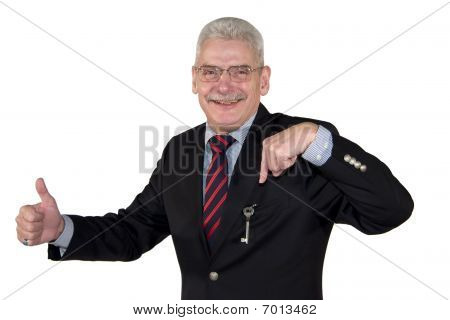 smiling senior manager pointing at key and posing thumbs up
