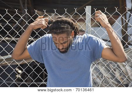 FERGUSON, MO/USA -  AUGUST 15, 2014: Man holds on to fence at the site of destroyed Quick Trip after Police Chief Thomas Jackson release of the name of the officer that shot Michael Brown.