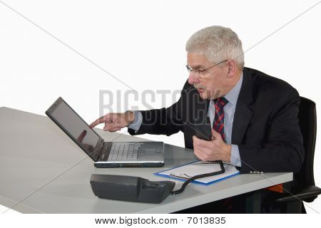 caucasian senior manager with laptop discussing on phone