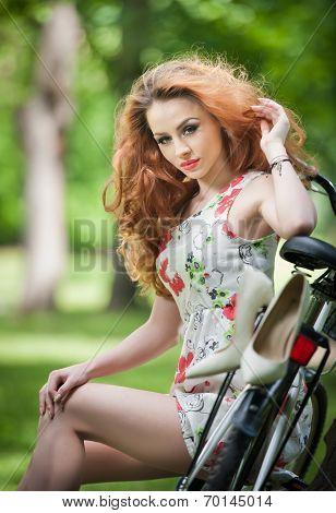 Beautiful girl wearing a nice short dress having fun in park with bicycle. Pretty long hair woman