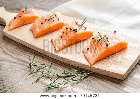 Raw Salmon Steaks On The Wooden Board
