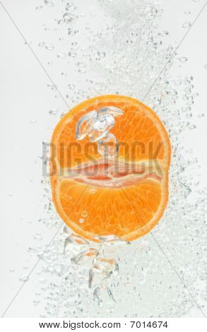 Orange (mandarin) Falling In Clear Water With Air Bubbles