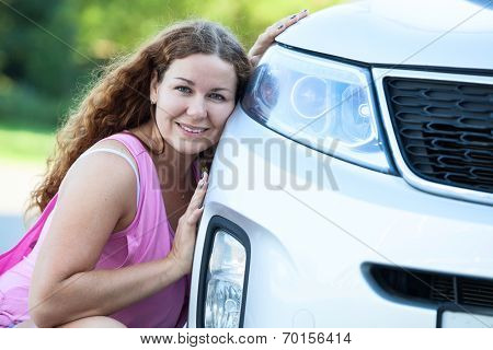Pretty Girl Sitting Her Cheek Against To The Bumper Of The Car