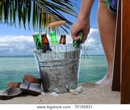Closeup of a man sitting in a chair at a tropical beach reaching into a bucket filled with ice cold beers. Only the mans leg and are are visible.