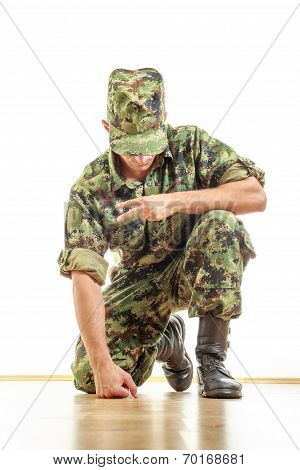 Soldier In Camouflage Uniform And Hat Kneeling On The Floor And Showing The Peace