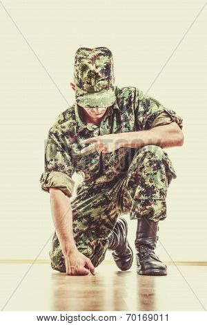 Soldier With Hidden Face In Green Camouflage Uniform And Hat Kneeling