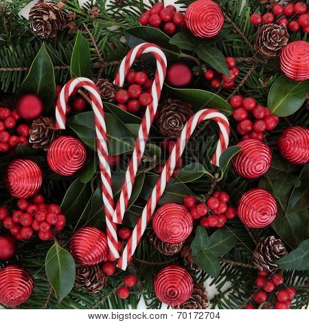 Christmas and winter flora background with red baubles, candy canes, holly and winter greenery.