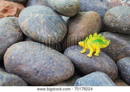 Plastic dinosaur on pebble stone