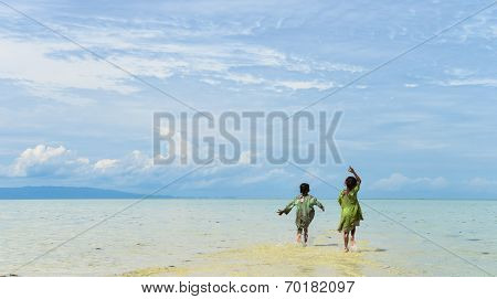 two native young girl running on tropical beach