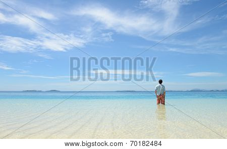 young man looking at horizon on tropical beach