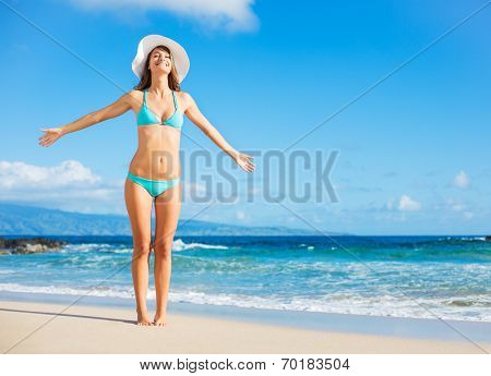 Relaxing each vacation. Beautiful woman in bikini enjoying perfect sunny day at the beach. Open arms, happiness, and bliss.