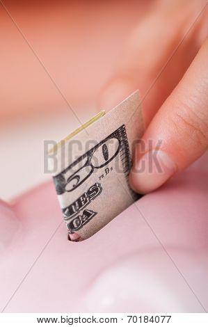 Hand Inserting 50 Dollar Bill In Piggybank