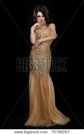 Formal Party. Glamorous Fashion Model In Elegant Golden Dress Over Black