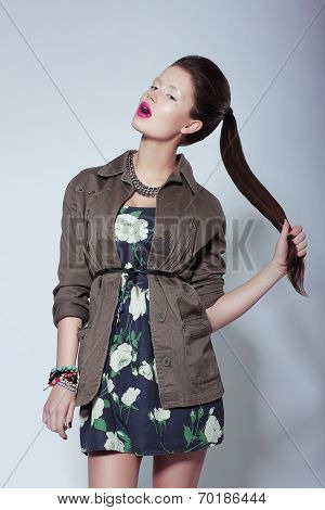 Trendy Fashion Model In Elegant Clothes Holding Her Tress
