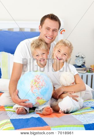 Cheerful Father And His Children Holding A Terretrial Globe