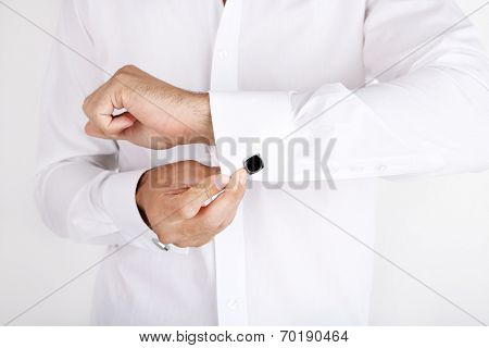 Man in white shirt doing collar button up