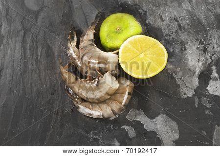 Fresh shrimp with lemon and lime against grey slate