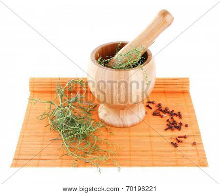 Mortar pounder of estragon on orange bamboo mat isolated on white