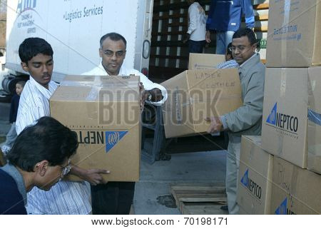 NEW YORK - JANUARY 1:  Sri Lankan-Americans from Boston unload clothing and food after arriving outside the Buddhist Vihara Temple to aid tsunami victims on January 1, 2005 in Queens Village, NY.