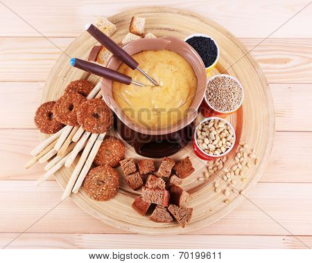 Fondue, biscuits, spices and rusks on bamboo plate on wooden background