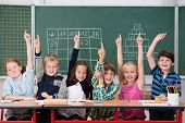 stock photo of youngster  - Enthusiastic group of young kids in class sitting in a row at their desk raising their hands in the air to show the know the answer to a question - JPG