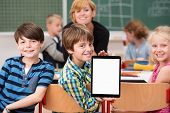 stock photo of classmates  - Little boy presenting a blank tablet in class turning in his chair to show it to the camera watched by smiling classmates - JPG