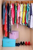 image of wardrobe  - Colorful clothes hanging in wardrobe - JPG
