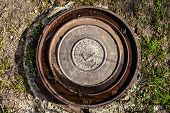 picture of manhole  - Manhole with rusty metal cover and water in its grooves - JPG