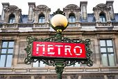 stock photo of front-entry  - Red art deco and lamp post Paris metro subway entry sign fronting the Louvre in Paris - JPG