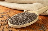 picture of tablespoon  - Organic chia seeds in a wooden spoon. Shallow depth of field focus in center area of spoon