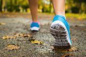 stock photo of wet feet  - Female athlete ready for autumn running challenge in park wet track - JPG